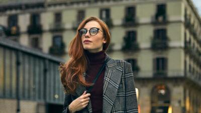 eine rothaarige Frau mit stilvoller schwarzer Brille