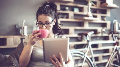 eine junge Frau mit Brille trinkt Kaffee und liest auf ihrem Tablet
