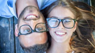ein junges Paar mit Brille liegt gemütlich auf einem Steg und lächelt in die Kamera